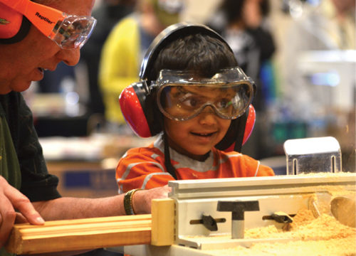 Member of NovaLabs Woodworkers guides young fairgoer on wood lathe. Photo Credit Emily Shaw